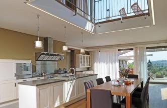 Prostorná kuchyň je otevřená ze všech stran, francouzská okna umožňují vstup na terasu a průhled do vyššího patra dovoluje mít přehled o všem, co se v domě děje