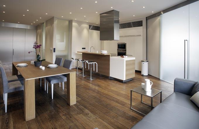 Kuchyňská část je od zbytku polyfunkční místnosti oddělena ostrůvkem v kombinaci přírodního dubu, corianu a MDF ve vysoce lesklém laku. Do kuchyňského prostoru se vešly veškeré důležité elektrospotřebiče. Úložné prostory jsou vzhledem k velikosti bytu velkorysé. Místnosti dominuje dubový stůl pro osm lidí