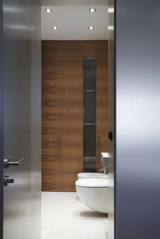 V bytě jsou dvě koupelny. Menší tzv. denní, je určena i pro hosty. Na podlaze je velkoformátová dlažba. Sanitární keramika bílé barvy je stejně jako zbytek interiéru tvarově minimalistická
