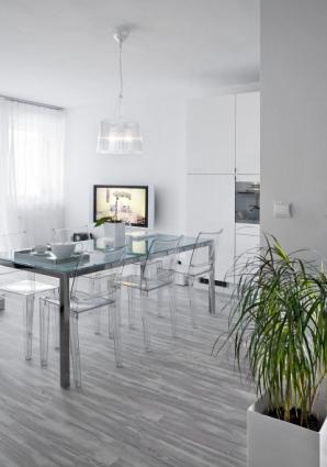 Útulné místnosti − tedy obývacímu pokoji s kuchyňským koutem dominuje velký stůl s transparentními židlemi La Marie (Kartell) od Philippa Starcka a osvětlení Bourgie, design Ferruccio Laviani (Kartell)