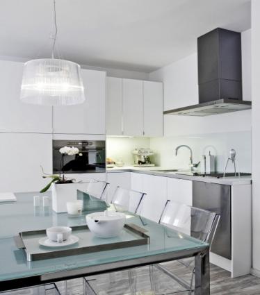 Kuchyňská linka v bílém vysokém lesku je vybavena spotřebiči 3 v 1. Majitel si nechal na zakázku vyrobit i speciální, téměř neviditelné úchyty
