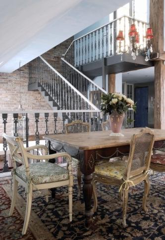 Jídelní kout vyvolává jižanskou atmosféru. Posezení u jídelního stolu nabízí pohled na zdobné schodiště vedoucí na terasu