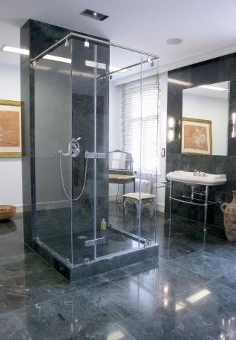 Jedna z koupelen působí na první pohled něžně a romanticky. Oblé tvary sanity se skvěle doplňují s minimalistickým sprchovým koutem. Koupelna je obložena přírodním kamenem