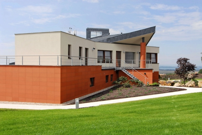"""Šipka zastřešení terasy míří daleko na horizont, na vrcholu střechy je patrná """"lucerna"""". Dojem z nestandardní tvorby umocňuje atypická jehlanová střecha hlavní hmoty domu"""