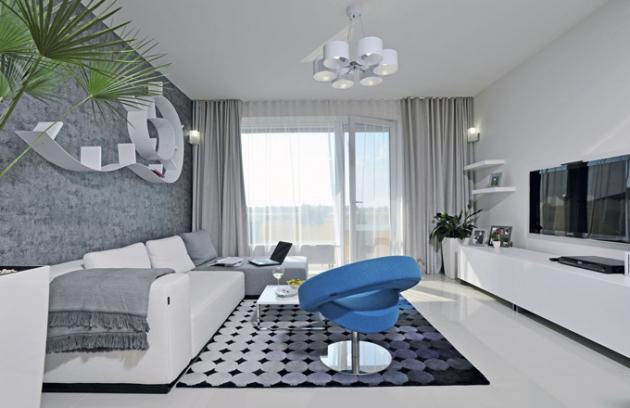 Do obývacího pokoje si majitelé vybrali variabilní pohovku s textilním potahem, kterou doplnili křesílkem Hello. Jeho výrazná barva příjemně narušuje neutrální ráz pokoje. Stěnu zdobí variabilní police Flexa