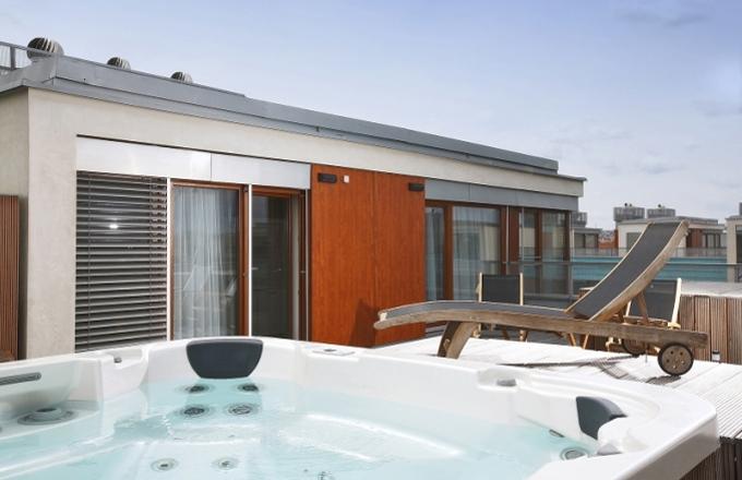 Součástí bytu je střešní terasa s vířivkou a malou zahrádkou