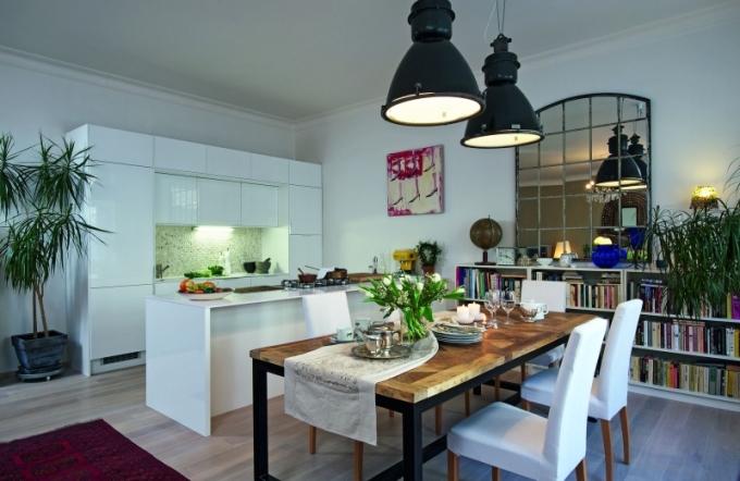Kuchyňská část je doplněna zrcadlem ze starého továrního okna, industriálními svítidly astředobodem je stůl sdeskou ze zámeckých parket