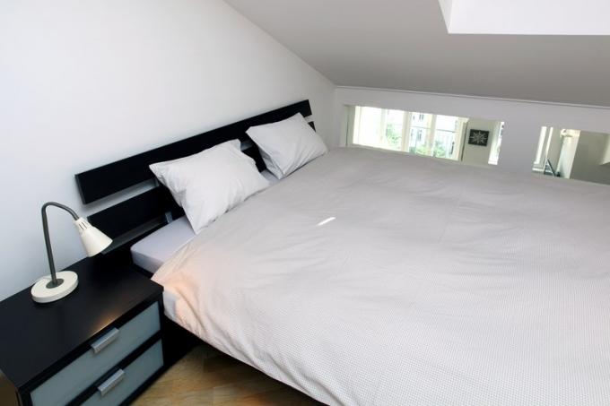 Z ložnice pro hosty, která je kromě koupelny jedinou místností v patře, je vidět do hlavního obytného prostoru