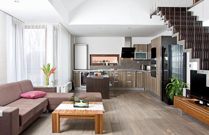 Oblíbeným interiérovým trendem posledních měsíců je kombinování několika druhů dřeva v odlišných barevných odstínech, což zvládli manželé Melicharovi výborně. Výsledkem je teplá a harmonická atmosféra v nejčastěji používaném prostoru