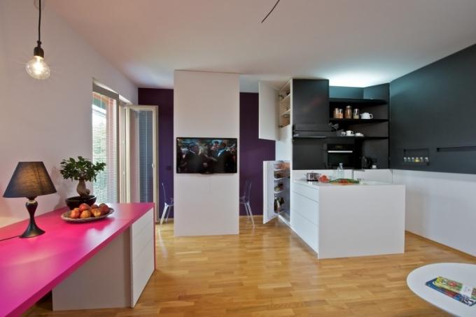 Kuchyňská i jídelní zóna se i přes skromnou dispozici bytu vměstnaly a jsou řešené velkoryse. Kuchyň je zhotovená z lakovaných MDF desek, pracovní deska je z corianu a je plnohodnotně vybavená spotřebiči značky Miele
