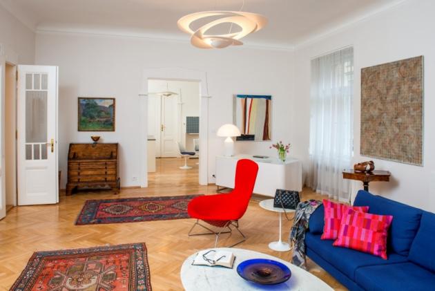 Obývací pokoj harmonicky spojuje předměty z různých období. Svěžímu konceptu sluší i perské koberce a starožitný nábytek. Dominantu pokoje tvoří lustr Pirce Suspension Light od značky Artemide