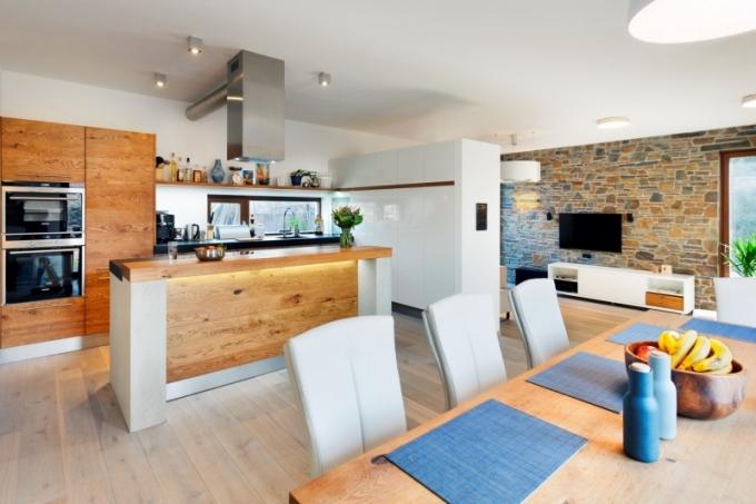 Kuchyňský ostrůvek opticky odděluje pracovní část kuchyně od přilehlého jídelního koutu. Příjemný kontrast k dubovému povrchu kuchyně tvoří bílá dvířka ve vysokém lesku. Jedna ze stěn v obývacím pokoji je obložena břidlicí, která se opakuje také na dlažbě v předsíni a v koupelně pro hosty