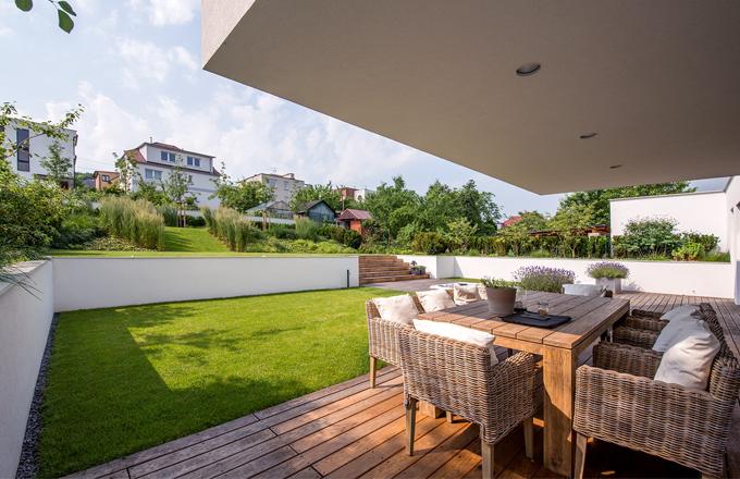 V teplých dnech se terasa promění v další obytný prostor. Příjemné stolování zajišťuje masivní týkový stůl a proutěné židle (Sempre)