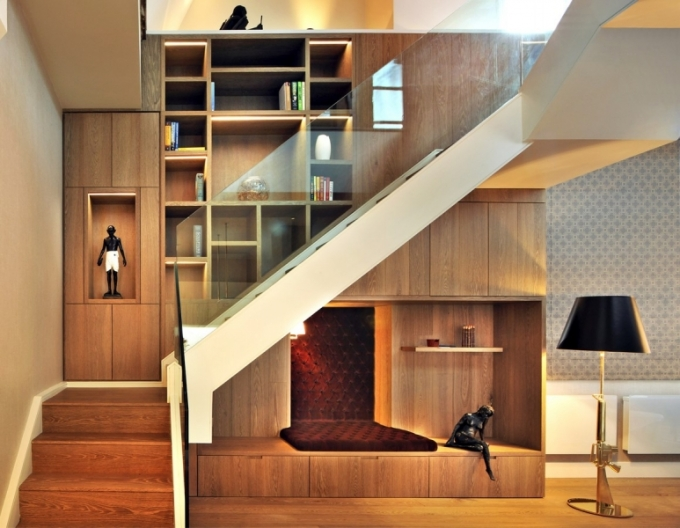 Asymetrické elegantní schodiště stoupající v prostoru využívá kombinace klasického dřeva na stupních a moderního skleněného zábradlí