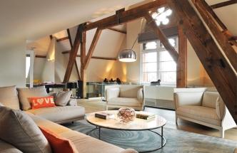 Velkorysá obývací zóna je prostřední částí třípodlažního loftu. Je vybavena nábytkem od designových značek Poltrona Frau, Knoll a Lema. Nejcennějším kusem je ale kulečníkový stůl