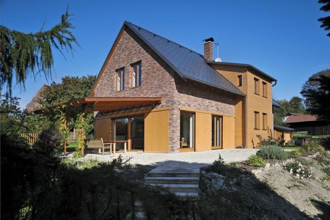 Na východní jižní straně lemuje dům velká kamenná terasa. Velké prosklené plochy jsou zvenku chráněny a stíněny posuvnými panely z dřevěných prken.