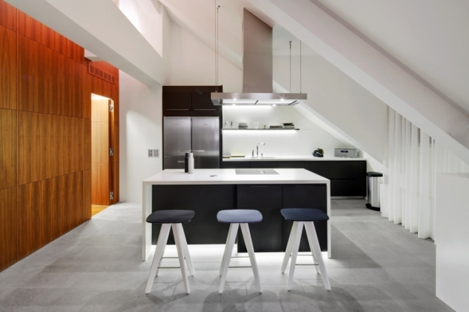 Po úpravě dispozice se kuchyň stala součástí obývacího pokoje, podlaha je z přírodního kamene, kuchyň od italského výrobce Varenna, pracovní ostrůvek z corianu s indukční deskou Miele