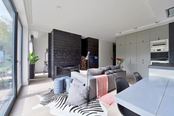 Klasickou nábytkovou stěnu zde nahradil krb s dřevěným obkladem. Součástí je také televizor a nad ním rafinovaně skryté úložné prostory. Čalouněná sedací souprava (Flexteam) je doplněná masivními dřevěnými lakovanými stolky HMD a lampou AJ Arne Jacobsena