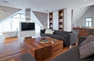Obývacímu prostoru vévodí sedací souprava Greta (design Ivana Dombková) čalouněná textilií a konferenční stolek z ořechového masivu. Lze ho rozdělit na čtyři samostatné díly a přesunout kamkoliv podle potřeby. Každý je opatřen zásuvkou s přítlakovým systémem