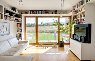 Velké prosklené stěny a výhled do volné přírody jsou nespornými výhodami bytu. Závěsná lampa je z BoConceptu (www.boconcept.com)
