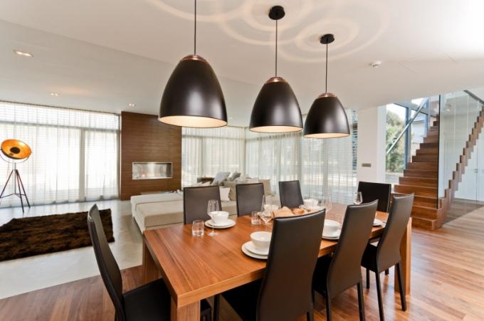 Jídelnu definuje pás dřevené podlahy z amerického ořechu. Je vybavená velkým jídelním stolem a černými koženými židlemi s vysokým opěrákem (Boconcept). Jako další opticky dělicí prvek prostoru byl použit set tří zavěšených černých svítidel (Boconcept)