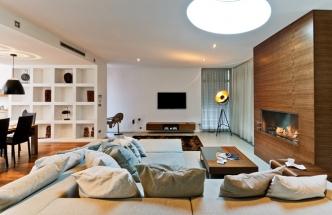 Obývacímu prostoru dominuje krb na biolíh v dřevěném obložení. Mimořádně velká sedací souprava je oboustranná a je zhotovená na míru daného prostoru. TV soustavu doplňují reproduktory zabudované v podhledu. Díky tomu zůstává celý prostor z estetického hlediska čistší. Prostor příjemně dotváří stojací lampa Captain (Rendl)