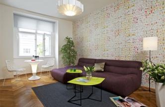 Stěnu zdobí tapeta s impresionistickým motivem od Elitis, závěsné svítidlo je z dílny značky Normann Copenhagen, stolek se svíticí podnoží od Infinity