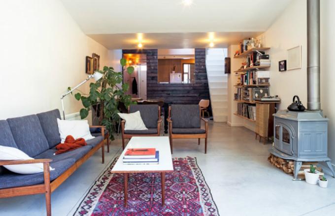 Obývací pokoj je zařízený ve stylu vintage s moderními prvky. Díky prosklené stěně a vchodu na zahradu je plný světla