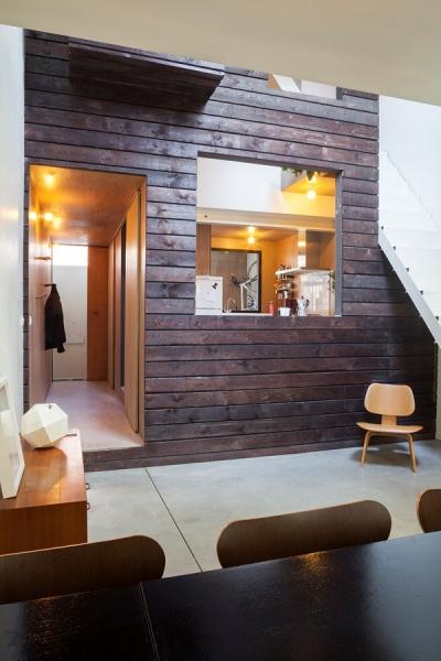 Kuchyň zabírá první úroveň vnitřního domu z hrubě opracovaných prken. Je z ní vidět do obývacího pokoje, takže ten, kdo vaří, má o všem výborný přehled