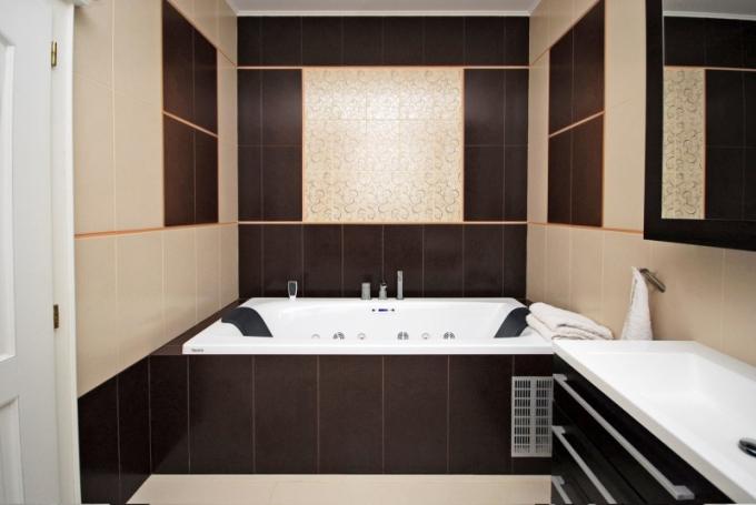 Koupelna má obdélníkový půdorys. Aby nepůsobila přeplněným dojmem, použila návrhářka k vaně pouze umyvadlový nábytek. Prostor opticky člení obklady s dekorem a střídání tmavých a světlých ploch