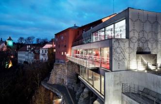 Původní omítnuté budovy doplňuje betonová přístavba s grafikou inspirovanou lidovými vzory. Velké prosklené plochy umožňují krásný výhled do údolí a na starou část města