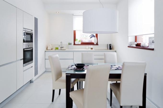Kuchyň si nechala Katarina vyrobit na míru. Pracovní deska je z umělého kamene. Bělost kuchyňské sestavy doplňuje tmavý jídelní stůl a odlišným prvkem jsou i parapety mořené do červených tónů a okenní rámy