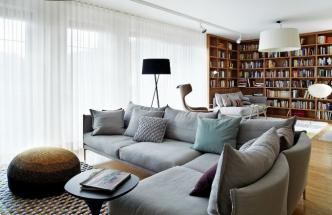 Obývacímu pokoji dominuje prostorná rohová knihovna, která ukrývá i radiátor za pohovkou. Posezení u knihovny a před televizí zajišťuje sedací nábytek Gentry navržený Patricií Urquiolou pro Moroso. Centrální osvětlení je doplněno pojízdnými reflektory od italského výrobce Flos a lampionem Akari 10A od Vitry