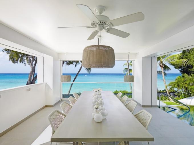 Otevřená jídelna nabízí osvěžující pohled na nekonečné množství lákavých odstínů moře a sytou zeleň tropických rostlin. Stůl vyrobený místními truhláři je doplněný vyplétanými židlemi značky Kettal