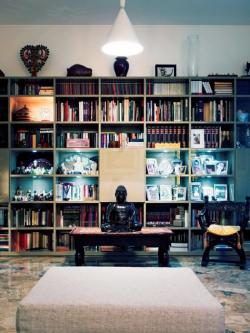 Protiváhu sezení tvoří knihovna přes celou protější stěnu. Najdeme tu rodinné fotografie, knihy všeho druhu od beletrie přes encyklopedie, knihy o umění, o moři a o sněhu. Největší pozornost však poutají thajské artefakty a sbírka téměř 90 soch Buddhy, symbolu života a stálé plodnosti.