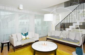Jednoduché zařízení obývacího pokoje ve světlém odstínu je oživené výrazným kobercem v limetkové barvě a interiér barevně oživují i textilní polštáře