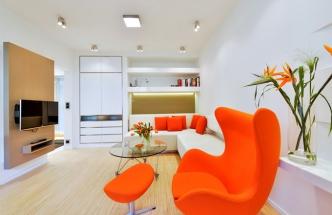 Konferenční stolek z čirého skla prostor opticky nezatěžuje. Je zhotovený na míru a díky elegantní podnoži s kolečky ho lze snadno přemisťovat. Legendární křeslo egg designéra Arne Jacobsena ve svěžím oranžovém odstínu poskytuje Haně pohodlnou náruč, kam ráda usedá a užívá si nově upravený prostor