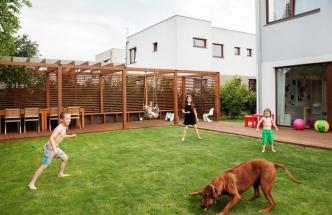 Zahrada je důležitou součástí domu. Pod dřevěnou pergolou se stoluje, na trávníku mají prostor děti z širokého sousedství