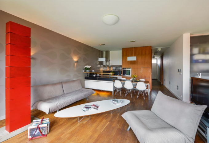 Pracovní ostrůvek je využívaný oboustranně. Z kuchyně poskytuje běžné úložné prostory a ze strany do obývacího pokoje slouží jako bar. Jídelní stůl ve shodném designu je doplněn plastovými židlemi DSR (Vitra) navrženými Charlesem a Ray Eamesovými