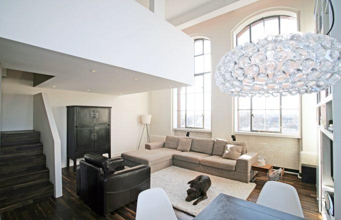 Nejsvětlejší částí bytu je obývací pokoj s ohromnými industriálními okny. Neutrální světle šedou pohovku doplňuje černé kožené křeslo, které majitelé pořídili v dražbě, a orientální sekretář Bílá modulová knihovna Billy z Ikea poskytuje dostatek úložného prostoru mezi okny. Starožitný jídelní stůl doplňují plastové židle od Ray a Charlese Eamesových a vše osvětluje závěsné svítidlo Caboche od Foscarini