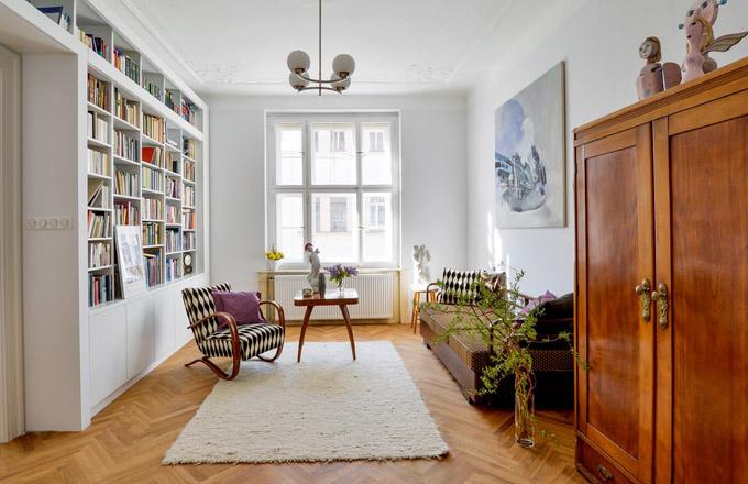 Průchod mezi jídelnou a obývacím pokojem byl rozšířen a zárubně jsou vyrobeny přesně podle těch původních. Knihovna (design Pavla Kosová) je zhotovená na míru danému prostoru tak, aby na sebe nestrhávala pozornost, která v této místnosti patří retro nábytku a obrazu Lucie Skřivánkové