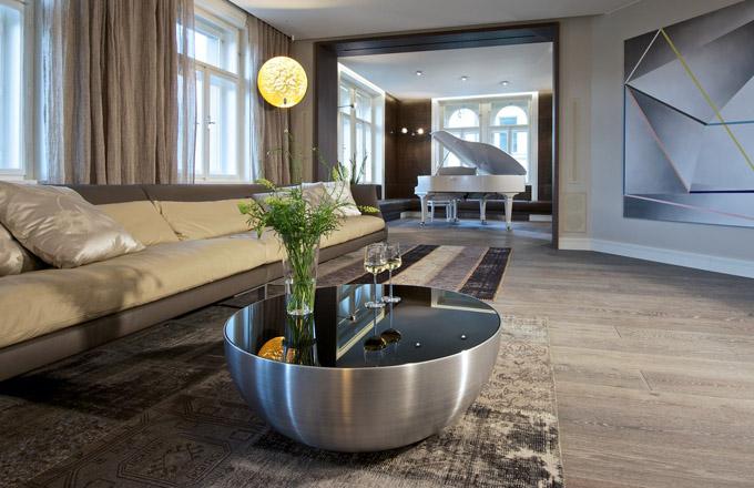 Hlavnímu prostoru dominuje repasovaný klavír August Förster, stěny kolem něj jsou pokryté obklady z kůže Burlington Brown od výrobce Sorensen. Podlahová prkna vhodná i pro podlahové vytápění instalované v celém bytě vyrobila na zakázku ve speciálním odstínu česká firma Magnum Parket