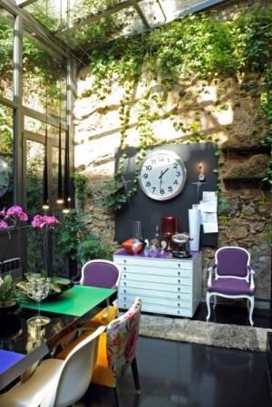 Zimní zahrada slouží také jako jídelna. Kolem stolu je celá plejáda židlí, z nichž dvě jsou starožitné. Bílá komoda je vyrobena podle Estrellina návrhu. Kamenná zeď je původní a byla součástí garáže
