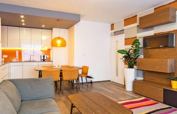 Zdenka si přála mít kuchyň spojenou s obývacím pokojem. Designérka sem navrhla bílou minimalistickou kuchyň ve vysokém lesku značky Rational a zvolila dispozici do tvaru L. Kuchyň vyniká na výrazném pozadí z kaleného skla v odvážném žlutooranžovém odstínu