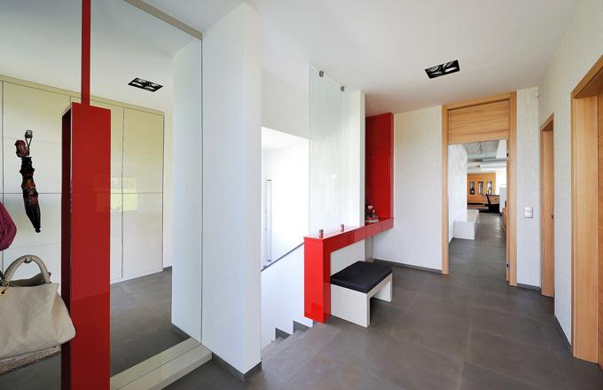 Členitá předsíň, která zahrnuje i schodiště, je vybavena atypickou sestavou skříněk z lakovaných MDF desek. Velká zrcadlová plocha pomáhá opticky zvětšit a prosvětlit prostor. Odkládací plochu se zásuvkami a sedátkem ocení zejména ženy, které nezanedbávají úpravu zevnějšku před odchodem z domu