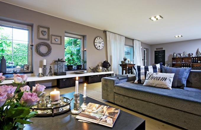 Obývací pokoj zabírá velkou část spodního podlaží. Dá se z něj vejít na kouzelnou terasu. Na dlouhé polici pod oknem je opět řada dekorativních předmětů a věcí, ke kterým má majitelka osobní vztah