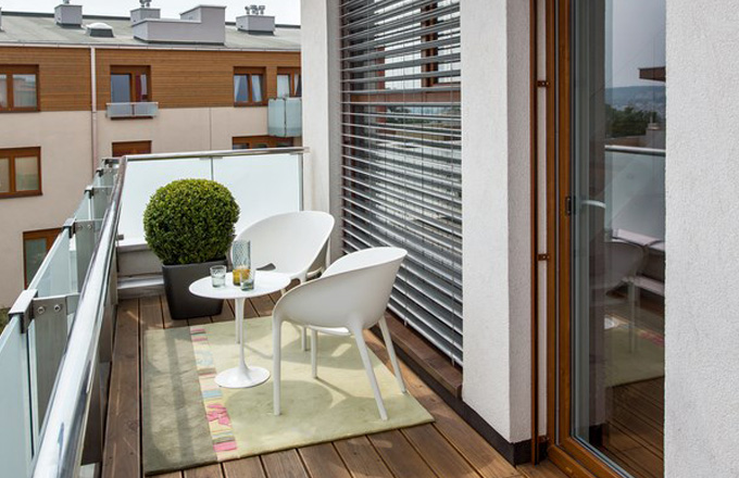 Terasa je vybavena kobercem Esprit, kulatým stolkem Low table (Knoll, design Eero Saarinen) a židlemi Soft Egg chair (Driade, design Philippe Starck)