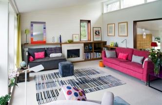 Barevné kombinace jsou odvážné a pokoj působí vesele a optimisticky. Výrazně růžová sedačka vypadá v interiéru zábavně, možná i díky barevným polštářům, které odvádějí pozornost od velké plochy