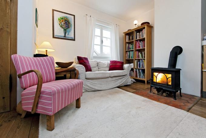 Vytápění domu zajišťuje moderní kotel s podavačem na dřevěné pelety, takže stačí přiložit jednou za dva týdny. Atmosféru interiéru dokreslují krbová kamna