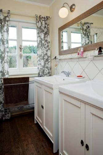 Závěsy, které prostor výrazně zútulňují, nechybí ani v koupelně s vanou